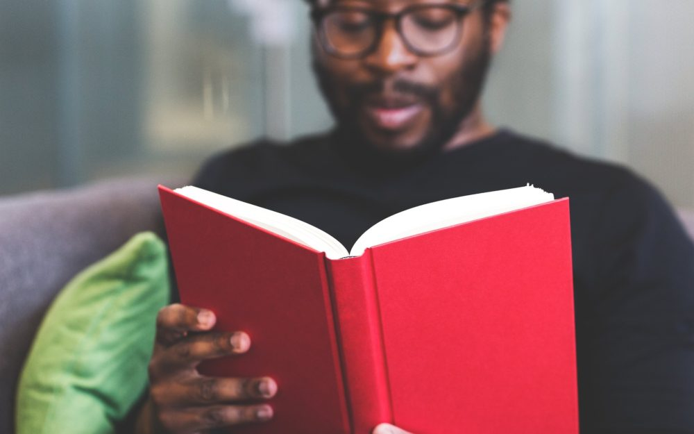 Stock image of Black man reading a red book wearing reading glasses