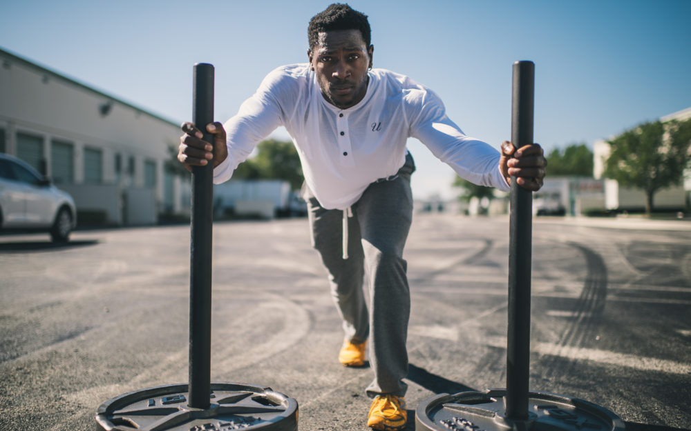 Stock image of Black man exercising outside with weights